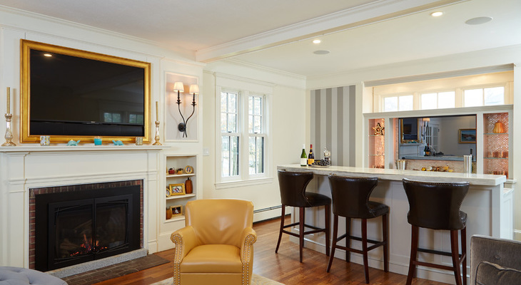 A formal living room gets a clever transformation into a casual family room with a large, featured custom bar.
